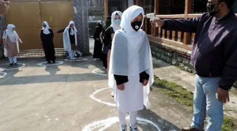 School authorities conduct thermal screening of students in wake of COVID19 in Srinagar on Monday as High and Higher Secondary Schools across the Kashmir valley re-opened after the outbreak of COVID19 pandemic