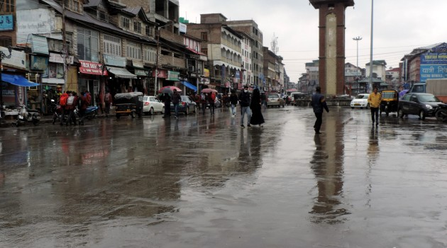 People holding umbrellas as incessant rains continued to lash Kashmir on the third day plunges the temperature and disrupt normal life on Wednesday
