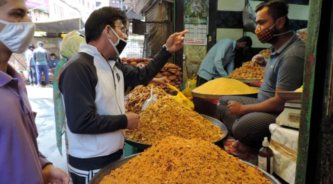 People purchasing Sweets and bakery items as authorities allowed selected shops to function  in view of  Eid-Ul-Fitr amid strict lockdown in place in Kashmir valley to combat the spread of COVID-19 positive cases on Monday.